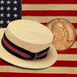 US flag, coin and boater hat illustrating American humanitarian aid